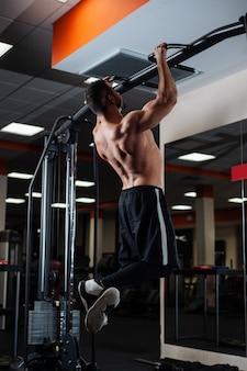 Atlético homem fazendo exercícios de pull-up em uma barra na academia