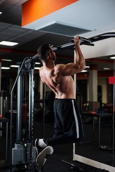 Atlético homem fazendo exercícios de pull-up em uma trave no ginásio