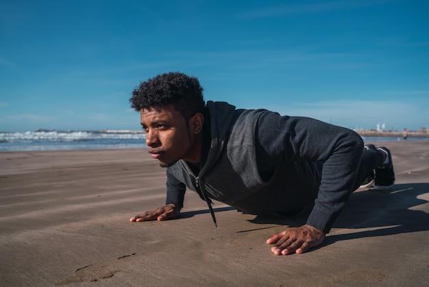 Atlético homem fazendo flexões na praia