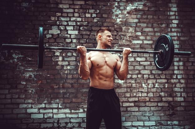 Atlético homem malhando com um barbell. força e motivação. exercício de bíceps.