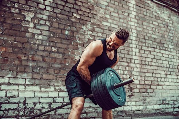 Atlético homem malhando com um barbell. força e motivação. exercício para os músculos das costas