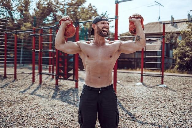 Atlético homem malhando com um kettlebell no quintal de ginásio de rua.