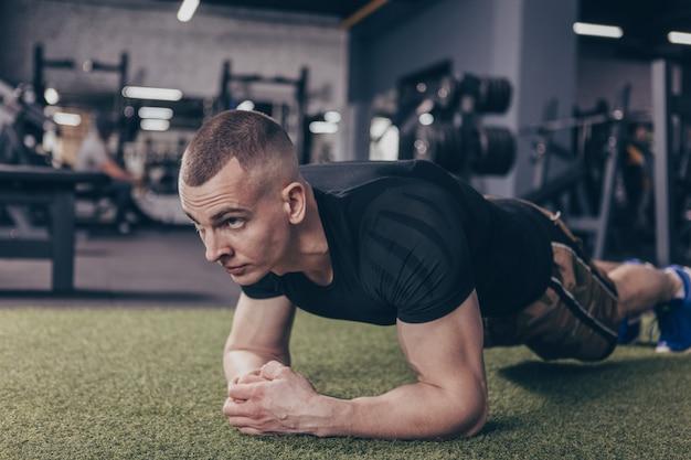 Atlético homem musculoso exercitando na academia