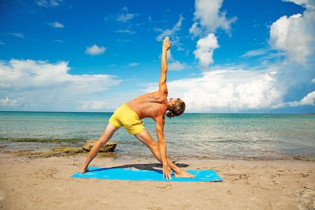 Atlético homem na praia fazendo exercícios de ioga fitness. elemento acroyoga para força e equilíbrio.