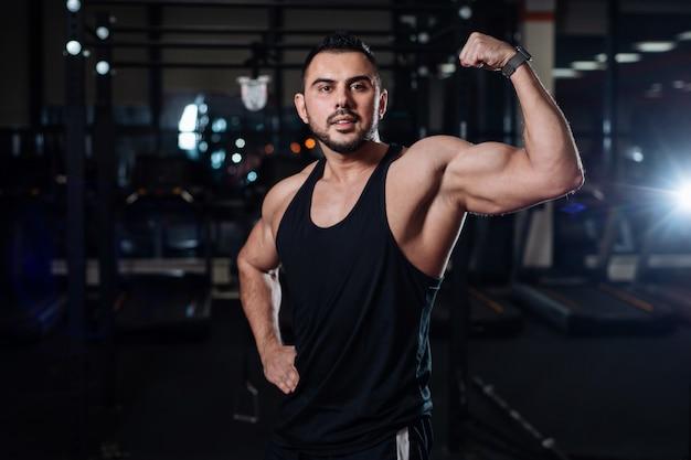 Atlético homem posando, exibindo seu bíceps no ginásio