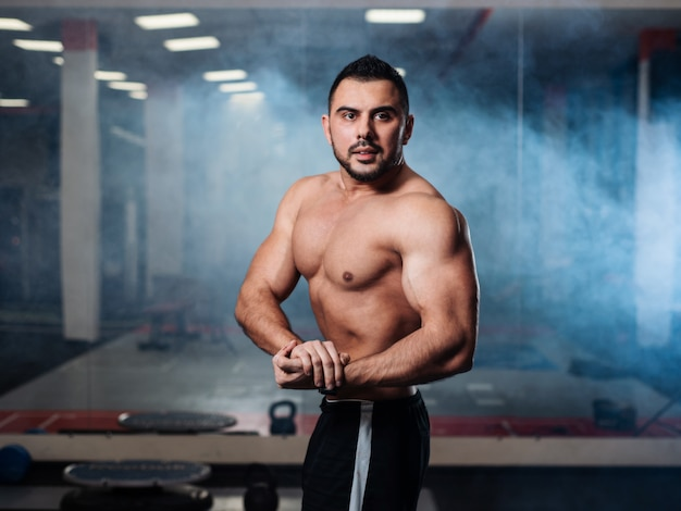 Atlético homem posando, exibindo seus músculos no ginásio