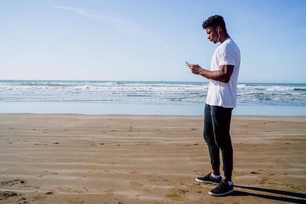 Atlético homem usando seu telefone celular