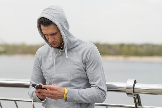 Atlético homem verificando seu telefone móvel