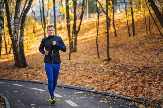 Atlético jovem correndo no parque durante a manhã de outono