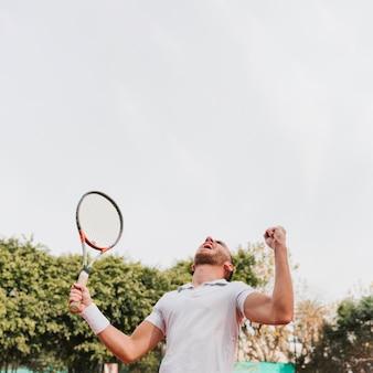 Atlético jovem rapaz ganhando um jogo de tênis