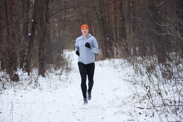 Atlético jovem runing na floresta de inverno e sorrindo