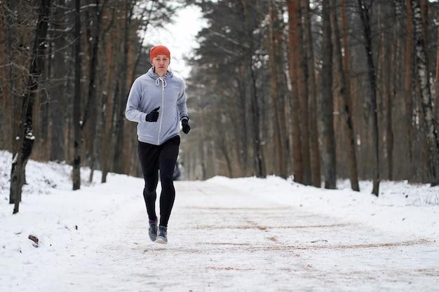 Atlético jovem runing na floresta de inverno