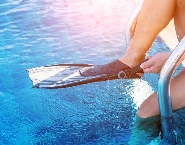 Atlético jovem vestindo nadadeiras à beira da piscina