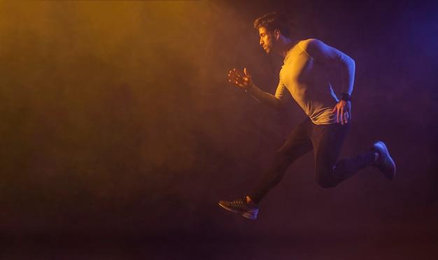 Atlético macho pulando no estúdio escuro