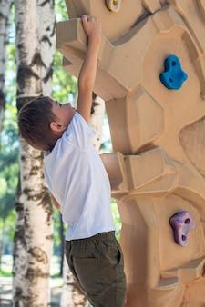 Atlético menino praticando escalada na parede de escalada no playground. parque de diversões para crianças