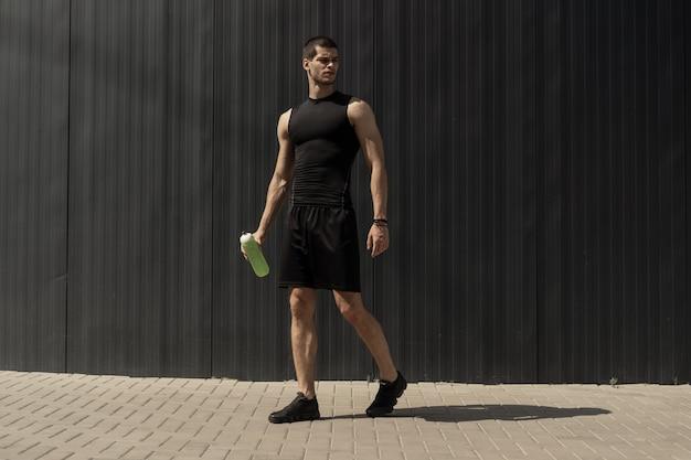 Atlético moderno jovem posando em uma parede metálica cinza