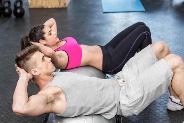 Atlético, mulher, e, homem, fazendo, crunches, em, crossfit, ginásio