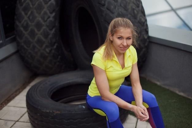 Atletismo, após o treino com pneu. sorrindo jovem desportista feminina sentada num pneu