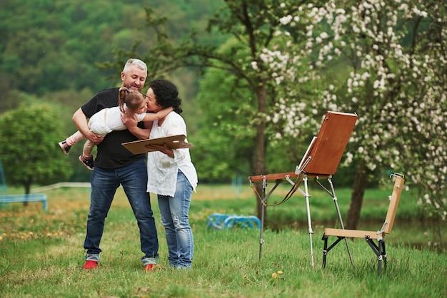 Atmosfera calma e tranquila. avó e avô se divertem ao ar livre com a neta. concepção de pintura