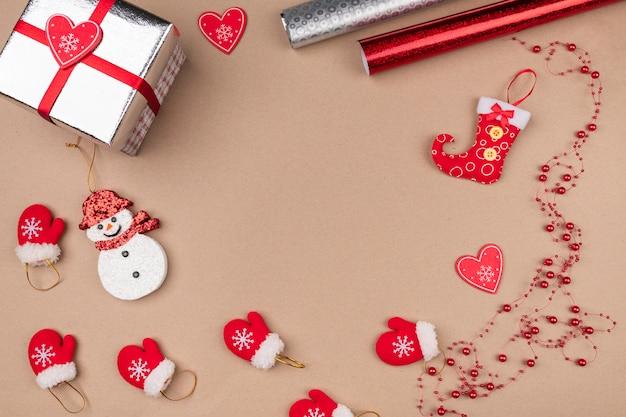 Atmosfera criativa. luvas pequenas vermelhas espalhadas sobre um fundo bege, juntamente com um presente em embalagem prateada, com um boneco de neve fofo, corações de papel e miçangas. ano novo. humor.