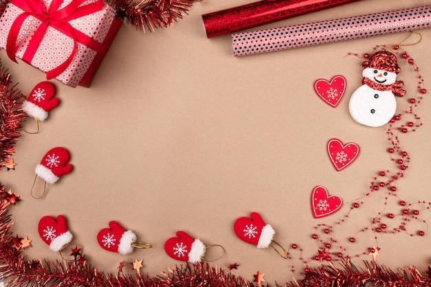 Atmosfera criativa. pequenas luvas vermelhas espalhadas em bege, juntamente com um presente em pé em uma embalagem prateada, com um boneco de neve fofo, corações de papel e miçangas cercados por enfeites de natal vermelhos.