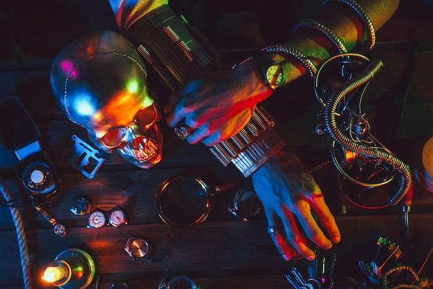 Atmosfera cyberpunk. mãos de um engenheiro inventor masculino em uma mesa com vários mecanismos steampunk, relógios, óculos e uma caveira