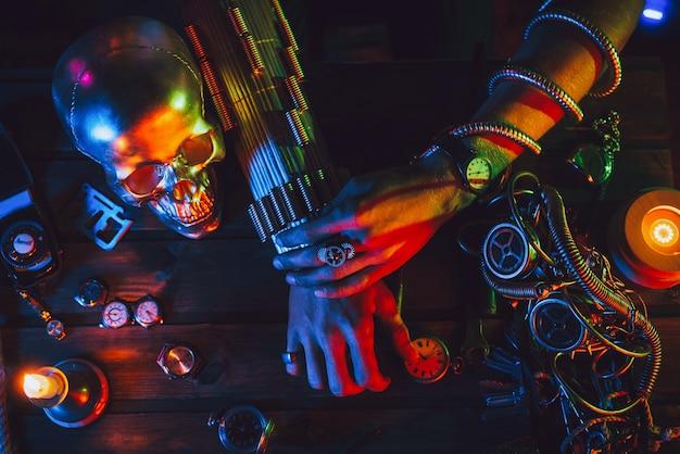 Atmosfera cyberpunk. mãos de um engenheiro inventor masculino em uma mesa com vários mecanismos steampunk
