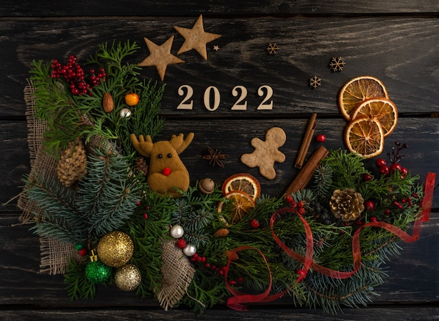 Atmosfera de ano novo 2022 composição cones de pinho árvore biscoitos de gengibre presentes