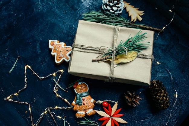 Atmosfera de ano novo o presente de ano novo e uma vela estão ao lado da árvore de natal e brinquedos de natal em fundo escuro