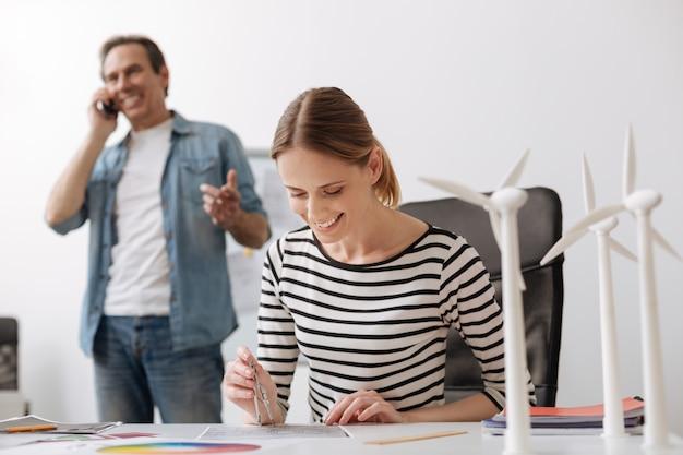 Atmosfera de escritório positiva. engenheira profissional alegre sentada à mesa e fazendo um desenho enquanto seu colega falando no telefone inteligente ao fundo