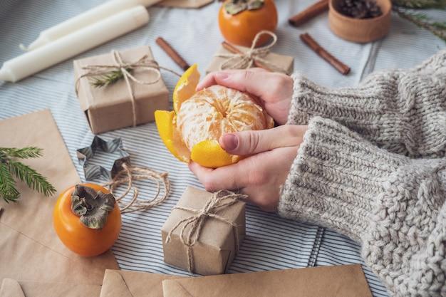 Atmosfera de natal, garota limpando tangerina entre presentes e árvores de natal, vista superior, close-up. plano de fundo de ano novo, tangerina nas mãos das mulheres. embalagem de presentes com materiais naturais.