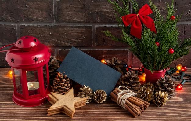 Atmosfera de natal ou ano novo composição cartão em branco pinhas cones guirlanda vela gingerbr ...