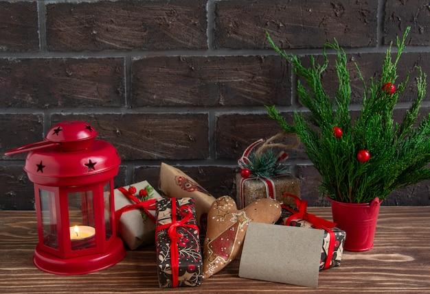 Atmosfera de natal ou ano novo pinhas de composição de pinhas queimando velas biscoitos de gengibre presentes co ...