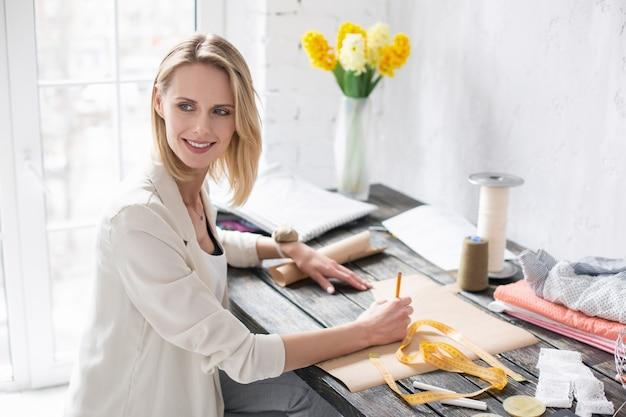 Atmosfera de trabalho. uma artesã talentosa bem-sucedida desenhando um padrão olhando para o lado
