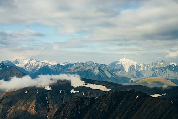 Atmosfera paisagem alpina com grandes montanhas rochosas nevadas ouro brilhantes e geleira gigante na hora de ouro. nuvens baixas na montanha de neve no nascer do sol. voando sobre montanhas acima das nuvens. maravilhoso cenário das montanhas.