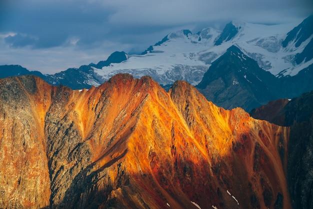 Atmosfera paisagem alpina com montanhas rochosas vermelhas na hora de ouro. vista panorâmica para grandes rochas laranja e montanhas nevadas gigantes com geleira no nascer do sol. maravilhoso cenário das montanhas. voando sobre montanhas.