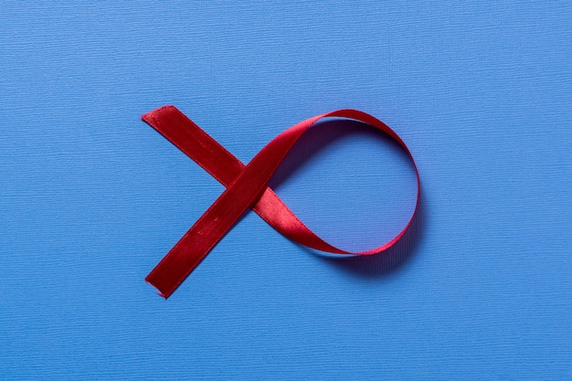 Atmosfera vermelha do cancro da mama da fita no espaço azul do fundo e da cópia para o texto.