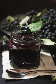 Atolamento de chokeberries pretos (aronia melanocarpa) e seus frutos na mesa escura. conservas caseiras.