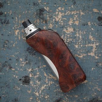 Atomizador de gotejamento rebuildable com mods de caixa regulada burl de sequóia natural estabilizada em um fundo de textura de madeira de pintura velha, dispositivo vaping, foco seletivo