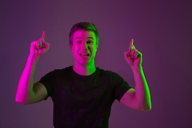 Atônito, apontando para a frente. copyspace. retrato do homem caucasiano no fundo roxo do estúdio em luz de néon. lindo modelo masculino de camisa preta. conceito de emoções humanas, expressão facial, vendas, anúncio.