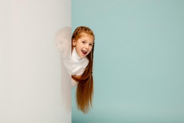 Atônito. criança feliz, garota isolada no fundo azul do estúdio. parece feliz, alegre. copyspace para anúncio. infância, educação, emoções, conceito de expressão facial. espiando por trás da parede.