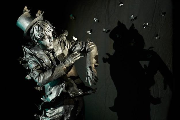 Ator mímico de comédia cuja aparência se assemelha a uma estátua de bronze tentando tirar borboletas artificiais que estão puxando suas roupas. pantomima profissional mostrando algum episódio de conto de fadas