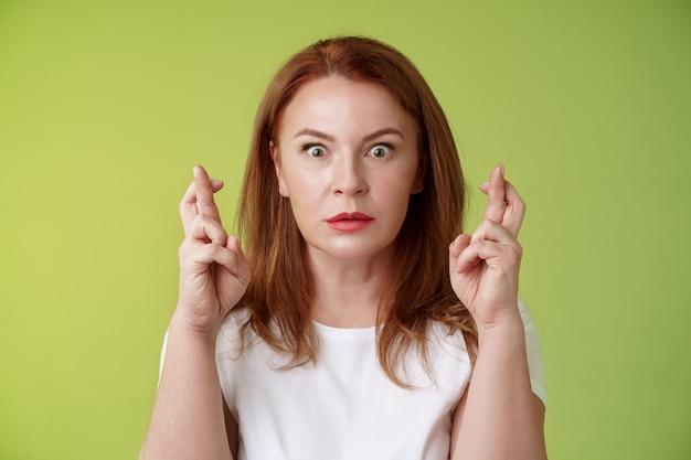 Atordoada, intensa e preocupada, mulher ruiva de meia-idade olha nervosamente esperando um resultado importante implorar que o sonho se torne realidade receber uma resposta positiva em pé estupor parede verde desejar boa sorte