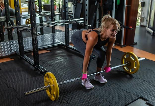 Atraente ajuste jovem esportes mulher com peso no ginásio. deadlift.