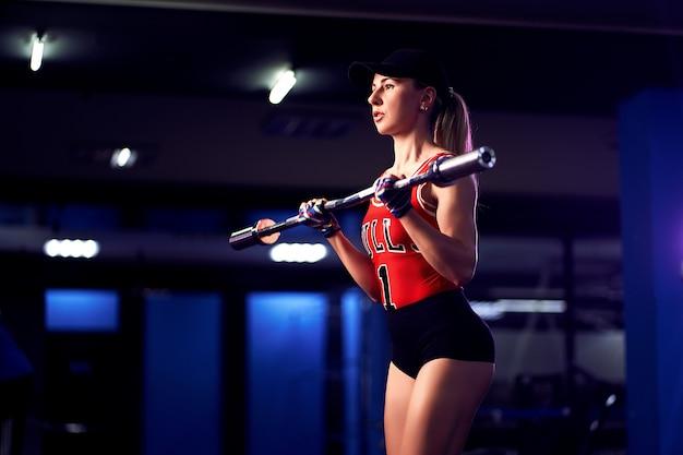 Atraente ajuste meia idade mulher atleta exercitar com barra no ginásio