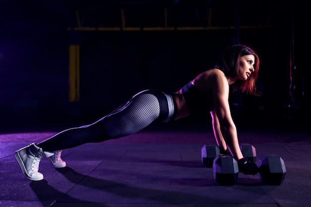 Atraente ajuste mulher de meia idade está fazendo exercício de prancha enquanto trabalha fora no ginásio