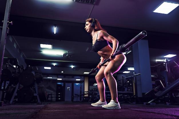 Atraente ajuste mulher sexy no ginásio agacha-se com um barbell. mulher treinando de volta