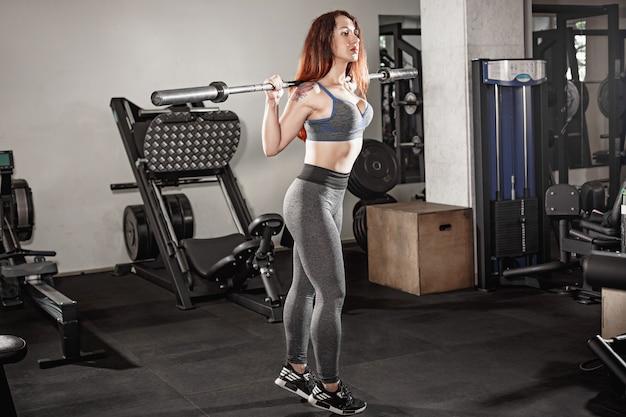Atraente ajuste mulher trabalha com halteres