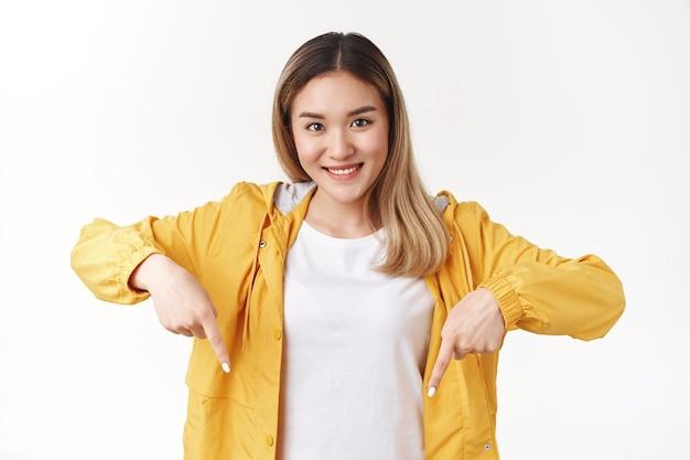 Atraente alegre boba loira asiática apontando para baixo o dedo indicador olha a câmera feliz otimista sorriso propor uma boa recomendação em pé na parede branca