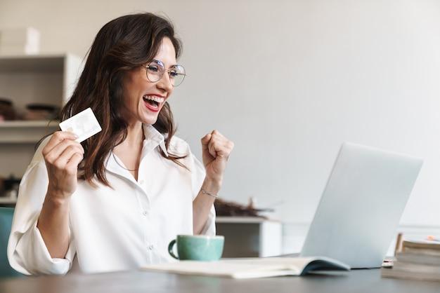 Atraente alegre jovem morena empresária sentada à mesa do café com o laptop dentro de casa, fazendo compras online com cartão de crédito